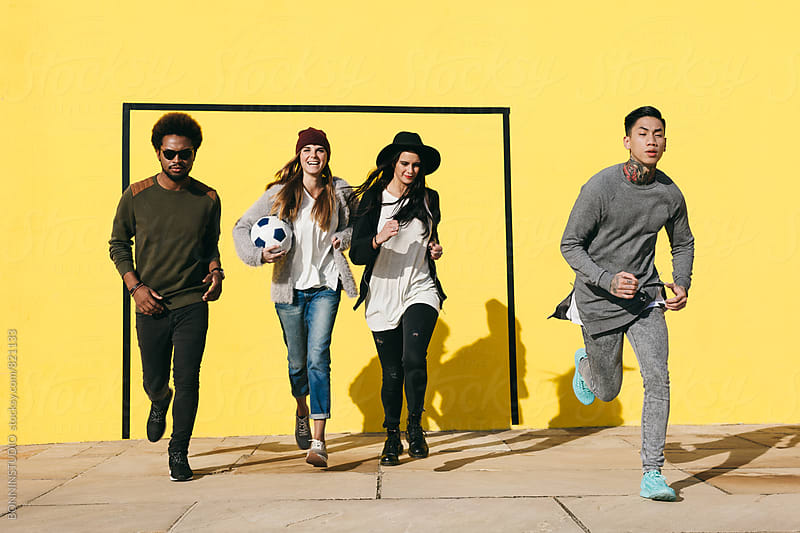 Group of friends having fun running in front of a yellow wall. by BONNINSTUDIO for Stocksy United
