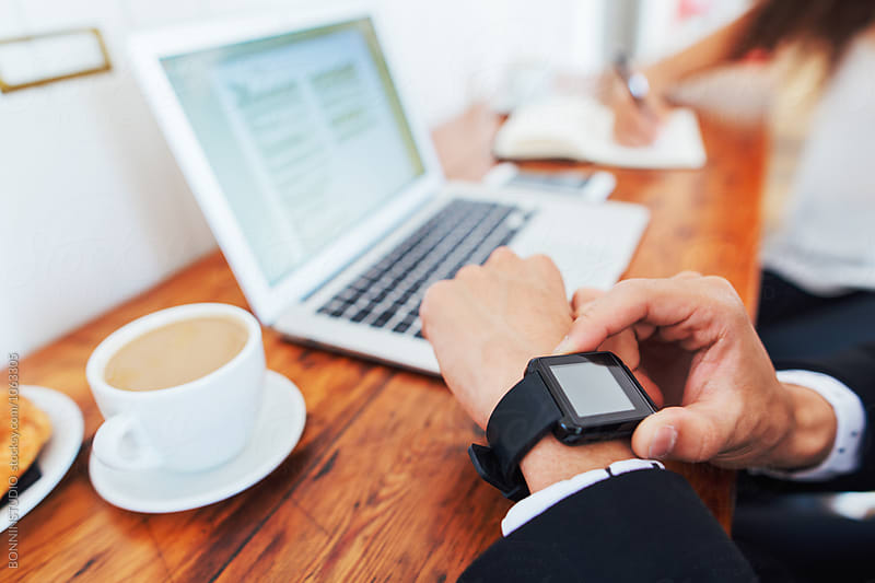 Closeup of a businessman touching his smart watch working in a coffee bar.  by BONNINSTUDIO for Stocksy United