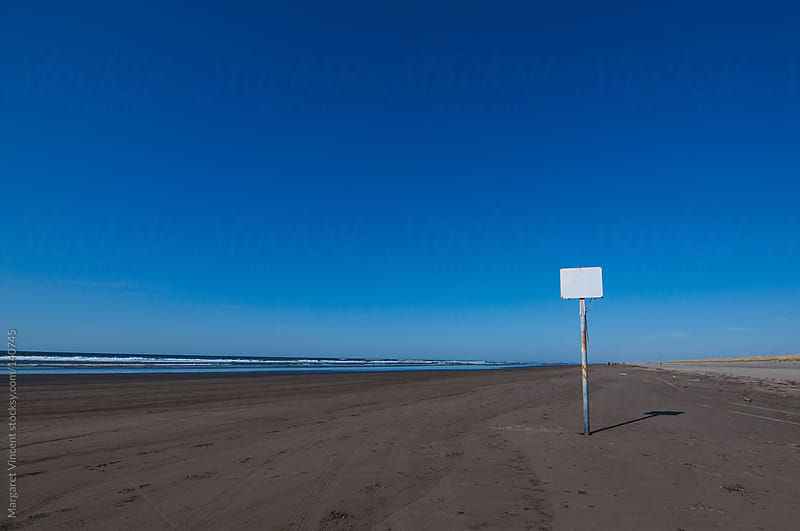 blank sign on an empty beach by Margaret Vincent for Stocksy United