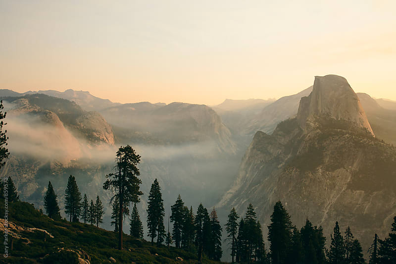Glacier Point views of Yosemite Nation Park with a morning haze as the sun comes up by Gary Parker for Stocksy United