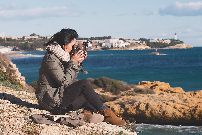 Side view of photographer taking shot with old camera at seaside by Guille Faingold for Stocksy United