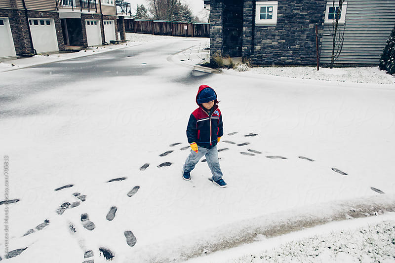 A young kid walking around the neighborhood after the first snowfall by Lawrence del Mundo for Stocksy United