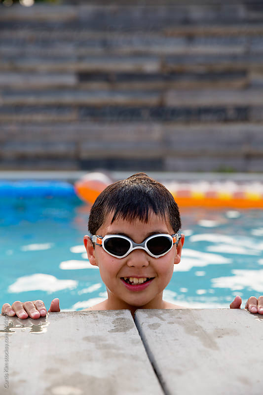 Young boy smiling in pool by Curtis Kim for Stocksy United