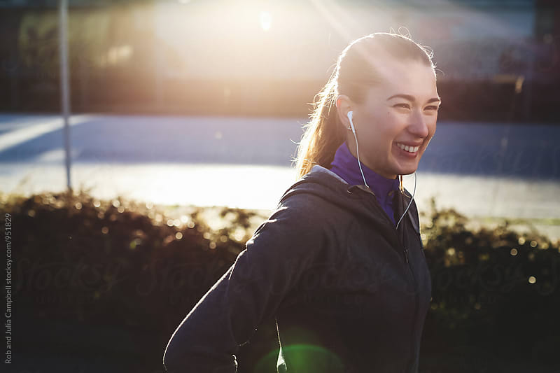 Young, happy caucasian woman smiling outside wearing sports clothes by Rob and Julia Campbell for Stocksy United