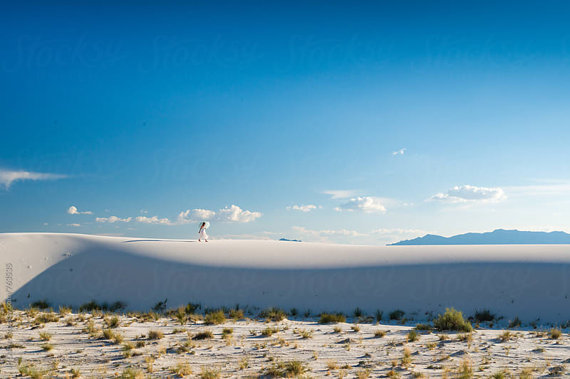Woman Walking Along Sand Dunes In White Sands National Monumant New Mexico with Vibrant Blue Sky by JP Danko for Stocksy United