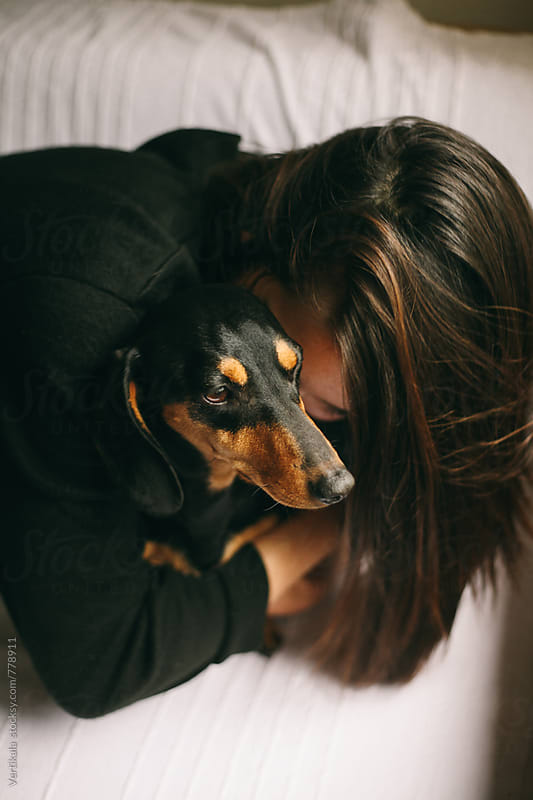 Brunette woman hugging her small black dog by Marija Mandic for Stocksy United