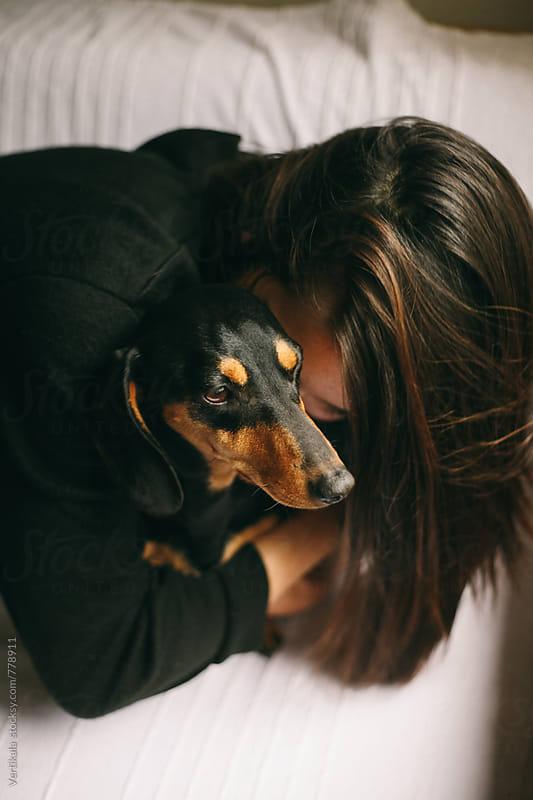 Brunette woman hugging her small black dog by VeaVea for Stocksy United