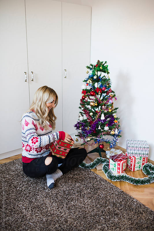 Happy young woman preparing Christmas tree by Jovana Rikalo for Stocksy United