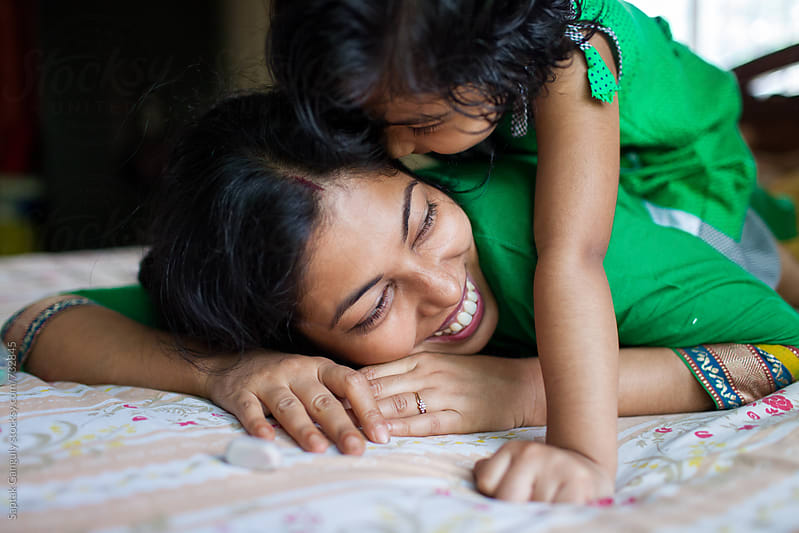 Cute little girl whispering into her Mother's ear by Saptak Ganguly for Stocksy United