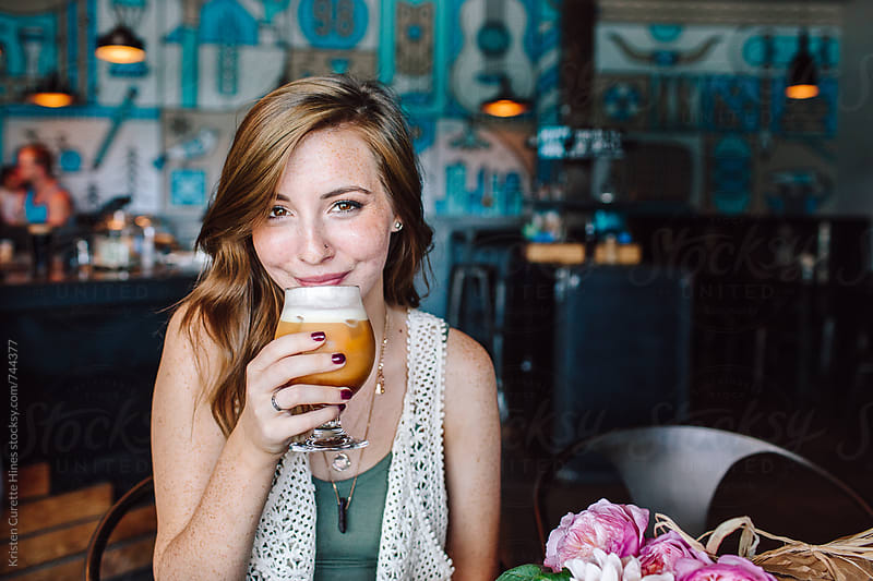 Young beautiful brunette girl drinking iced coffee and having fun. by Kristen Curette Hines for Stocksy United