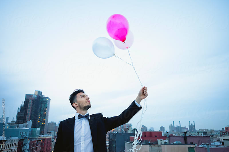 Young Man in a Suit with Balloons against New York Skyline by Joselito Briones for Stocksy United