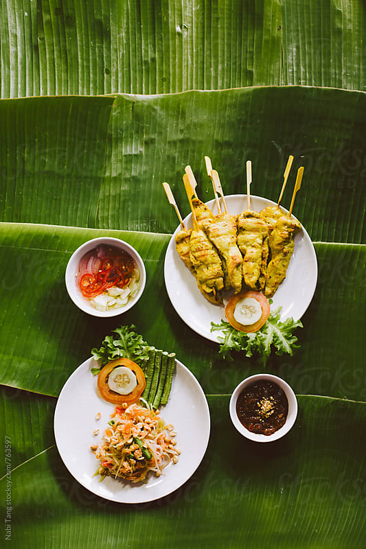 Som tam and chicken satay with vinegar and peanut sauce on banana leaves by Nabi Tang for Stocksy United