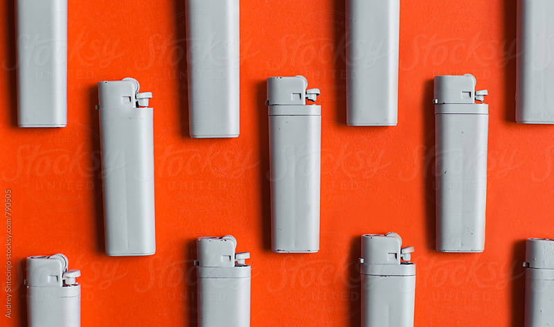 Organised white lighters on red/orange backgorund by Audrey Shtecinjo for Stocksy United