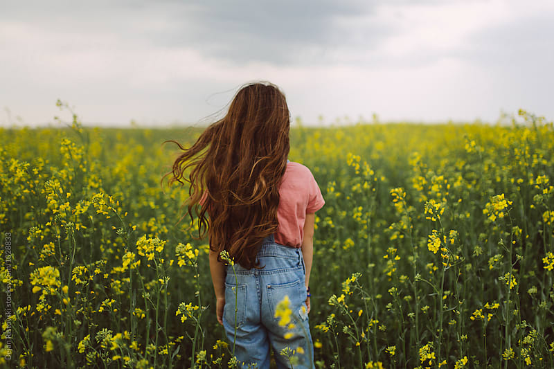 Girl standing in a field. by Dejan Ristovski for Stocksy United