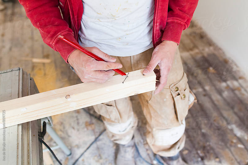 Worker or handyman writing the measurements on a piece of wood, for sawing by Ivo de Bruijn for Stocksy United