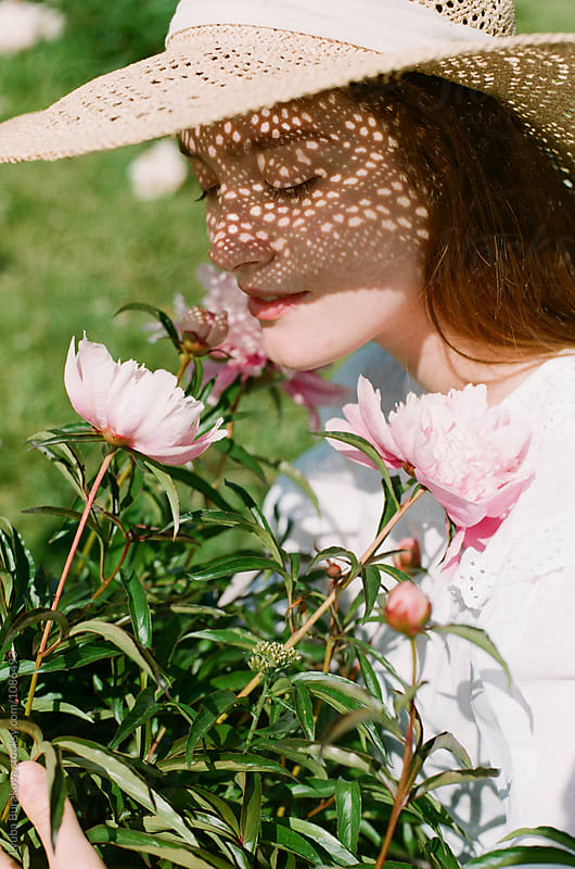 Young woman smells peonies by Lyuba Burakova for Stocksy United