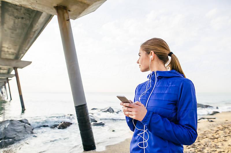 Runner woman listening music on her phone. by BONNINSTUDIO for Stocksy United