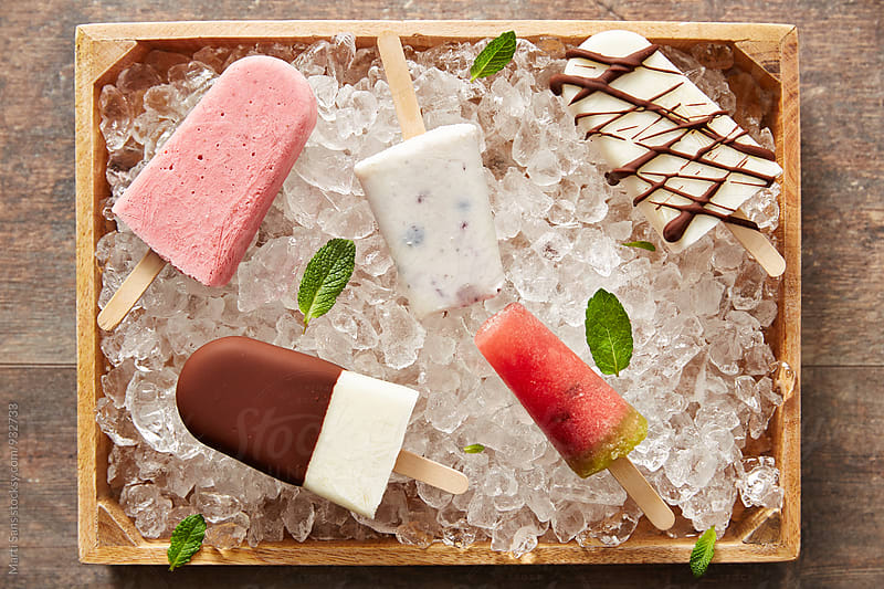 Five different popsicles on ice in basket by Martí Sans for Stocksy United