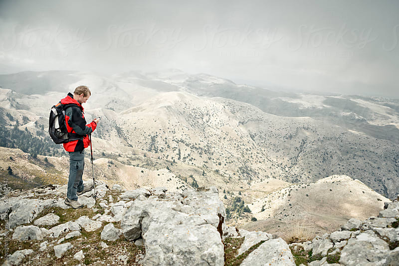 Hiker Using Camera Phone on Mountaintop by Stephen Morris for Stocksy United