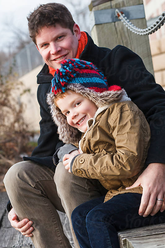 Father Sits with Arm Wrapped Around Son by Holly Clark for Stocksy United