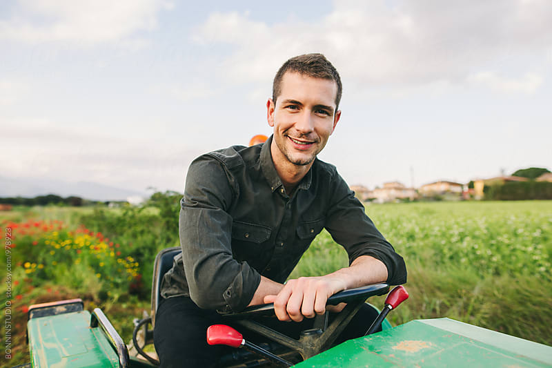 Portrait of a man with tractor in a green field. by BONNINSTUDIO for Stocksy United