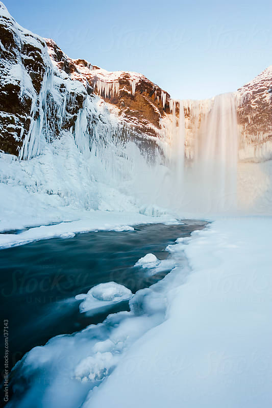 Iceland, Skogar, Skogafoss, Skogafoss waterfall surrounded by snow and ice in winter by Gavin Hellier for Stocksy United