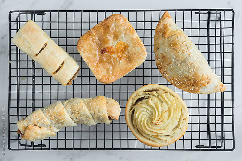 bakery savoury pastries on a wire rack by Gillian Vann for Stocksy United