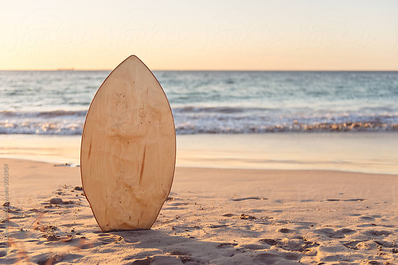 Skim board in the sand at the beach at sunset by Angela Lumsden for Stocksy United