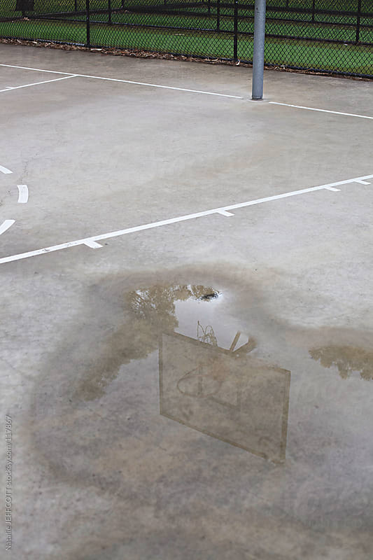puddle on the ground reflects basketball hoop by Natalie JEFFCOTT for Stocksy United