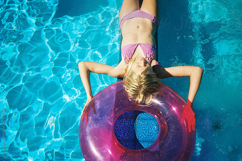 girl laying with pink floaty in blue swimming pool by wendy laurel for Stocksy United