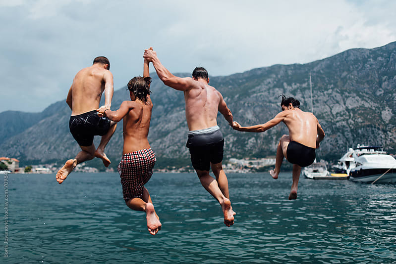 Group of men jumping in to the sea by Boris Jovanovic for Stocksy United