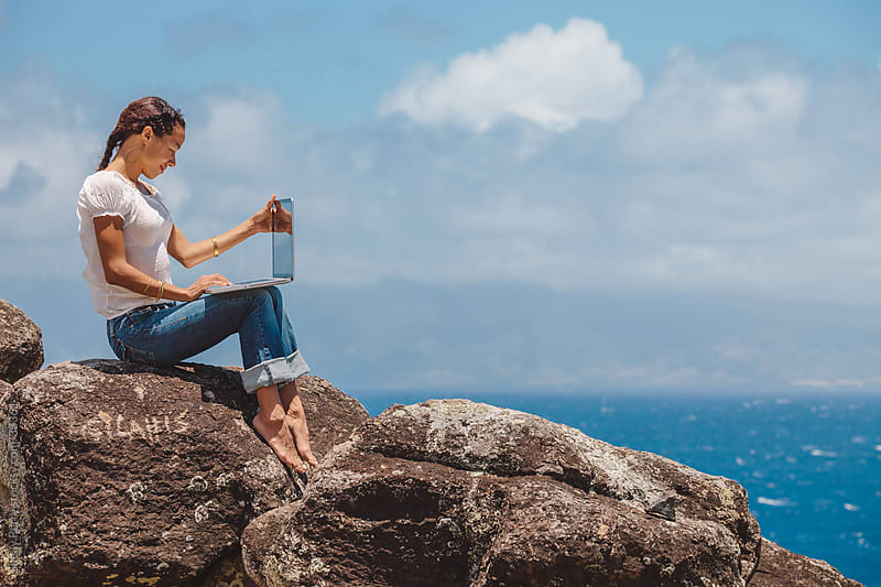 A casual young woman working on a laptop above the ocean. by Shelly Perry for Stocksy United