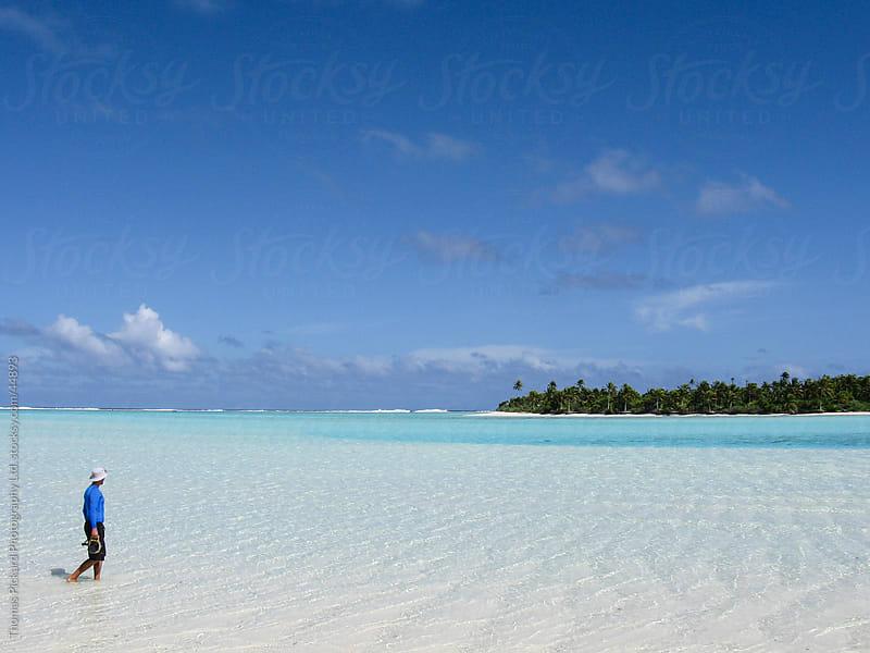 Photographer with waterhousing walking through a lagoon, Aitutak by Thomas Pickard for Stocksy United