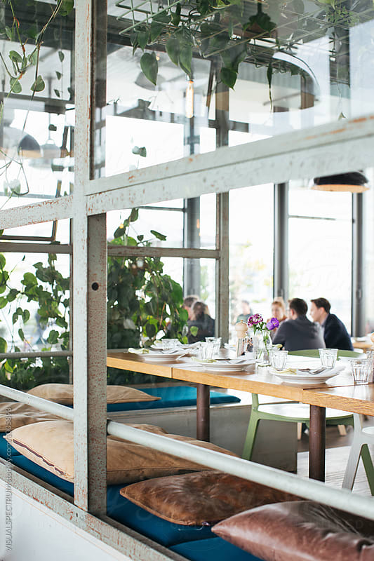 Set Table With Defocused Group of People in Stylish Bright Restaurant by Julien L. Balmer for Stocksy United