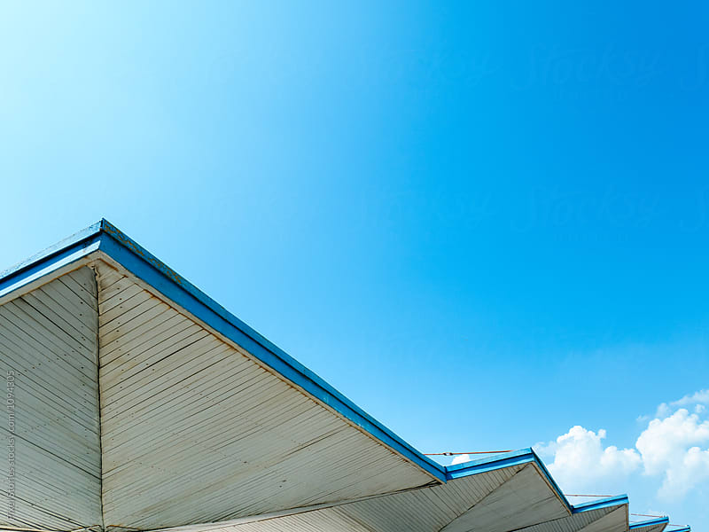 Communist-era bus stop shelter against blue sky by Pixel Stories for Stocksy United