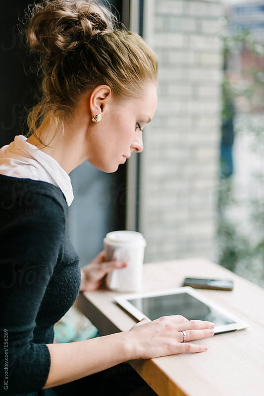 Young business woman using technology sitting at cafe by GIC for Stocksy United