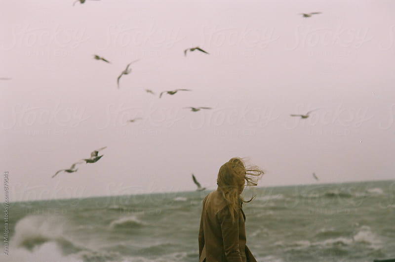 A back portrait of blond woman in front of winter stormy sea by Anna Malgina for Stocksy United