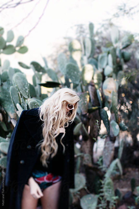 Blonde girl standing in front of cactus by Matt and Tish for Stocksy United