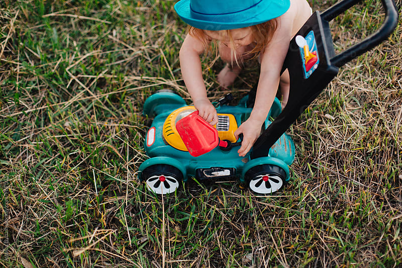 Toddler girl in diaper playing outside with pretend lawnmower. by Jessica Byrum for Stocksy United