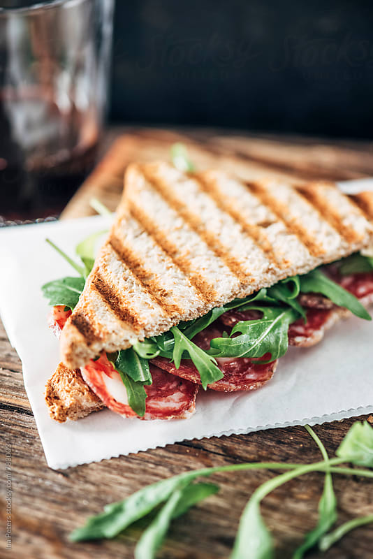 Food: Grilled sandwich with salami and rocket salad by Ina Peters for Stocksy United