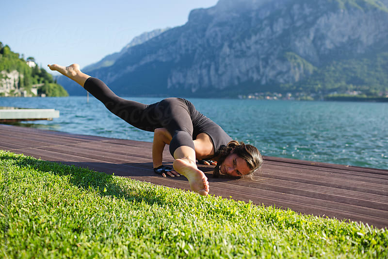 Woman doing  yoga pose: Eka Pada Koundinyasana by michela ravasio for Stocksy United