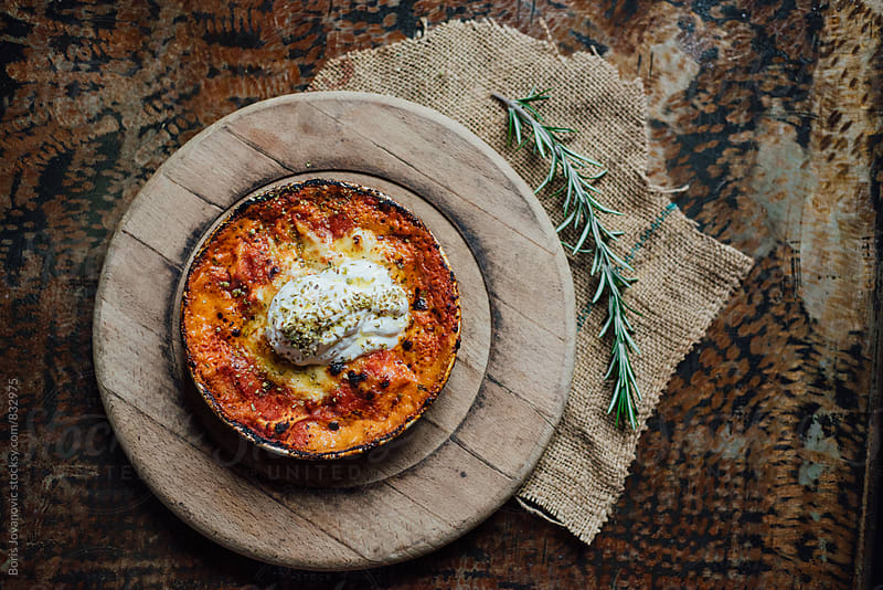 Lasagna meal in the rustic plate on wooden pad by Boris Jovanovic for Stocksy United