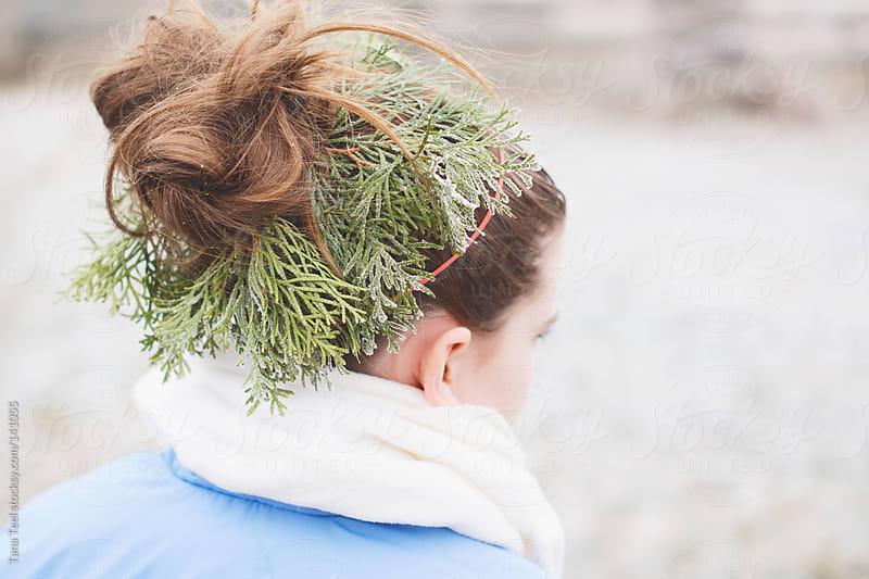 A frosty evergreen wreath adorns a girl's hair bun by Tana Teel for Stocksy United