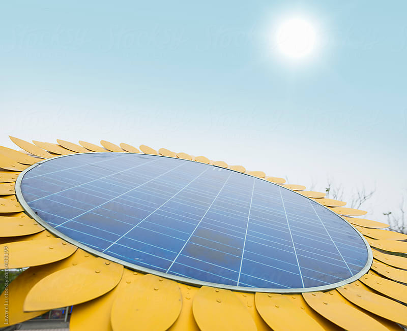 Solar panel with sunflower shape under sky and sun by Lawren Lu for Stocksy United