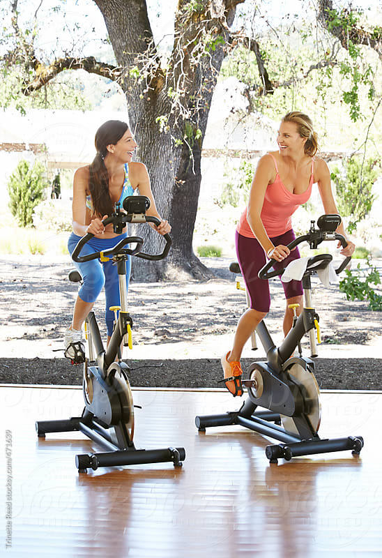 Happy Friends Working Out On Exercise Bike At Health Club by Trinette Reed for Stocksy United