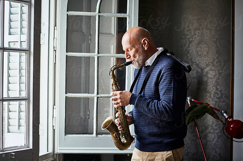 Senior Man Playing Saxophone By Window by ALTO IMAGES for Stocksy United