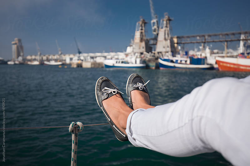 Young woman wearing boat shoes with laces tied and feet back relaxing on yacht floating on the ocean with boats in harbour port by Jonathan Caramanus for Stocksy United