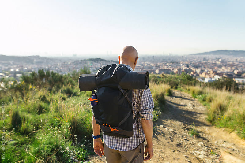 Senior man hiking on a mountain trail over the city. by BONNINSTUDIO for Stocksy United