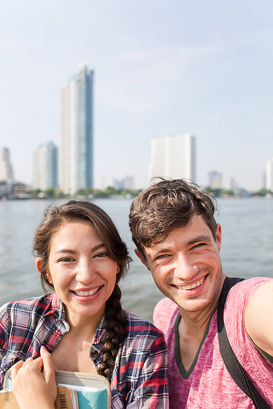 A smiling couple takes a selfie by Jovo Jovanovic for Stocksy United