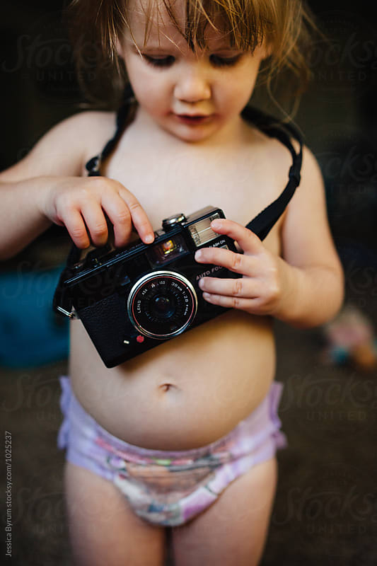 Toddler girl playing with old camera by Jessica Byrum for Stocksy United